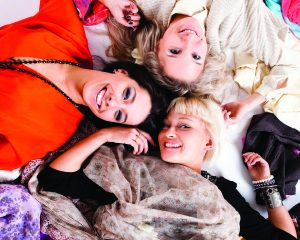 Three girls smiling while lying on a background of clothes