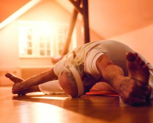 Senior man exercising Yoga in wide angle seated forward bend position.