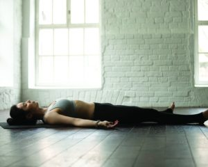 Young attractive yogi woman practicing yoga exercises concept, lying in Dead Body, Savasana, Corpse pose, resting after working out, wearing sportswear, full length, white loft studio background