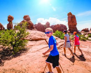 A happy family hiking together in the beautiful rock formations of Arches National Park. Walking along a scenic trail with large rock unique formations in the background