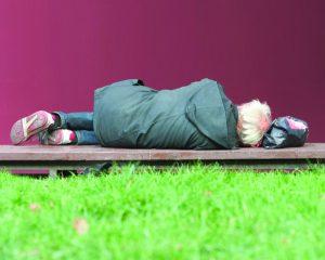 Homeless man lying on the bench.