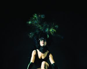 Woman with extraordinary Peacock Feather Hat performing with a huge wall clock, showing the time with her leg. Surreal. Bizarre Performance Art Portrait.