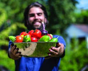 A close-up perspective of a man gardener in a blue shirt, carrying a bowl of vegetables in front of him. The man gardener is smiling and holds a stainless steel bowl with an assortment of vegetables, tomatoes, peppers, cucumber and onions. The background garden is out of focus.